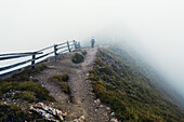 Hiker surrounded by thick fog, Puez-Geisler Nature Park, Dolomites, Unesco world heritage, South Tyrol, Italy