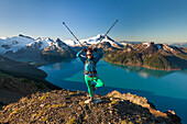 A backpacker makes a funny pose with her poles on the summit of Panorama Ridge in Garibaldi Provincial Park, British Columbia, Canada.