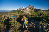 A photographer takes a picture of a young woman backpacking on the Panorama Ridge Trail with Black Tusk Mountain in the background in Garibaldi Provincial Park, British Columbia, Canada.