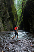 An adult woman taking the only route into the Oneonta Gorge--straight through it.  Portland, Oregon.