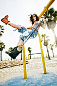 Mixed race woman standing on swing at beach