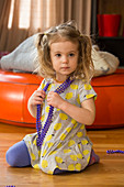 Caucasian preschooler girl playing dress-up with necklace