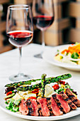 Plate of grilled meat and asparagus salad with wine
