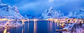 Panorama of snowy fisher village of Reine in the blue dusk in winter, Moskenesoy, Lofoten, Norway, Scandinavia