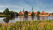 View over the lake Slotssøen to the water castle Frederiksborg on a summer day, Hillerød, Hovedstaden, Denmark