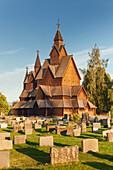 Heddal stave church with grave stones in the evening sun in summer, Notodden, Telemark, Norway, Scandinavia