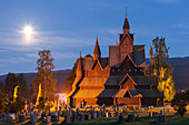 Heddal stave church with grave stones in a summer night with full moon, Notodden, Telemark, Norway, Scandinavia