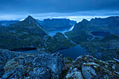View from the edge of the Hermannsdalstinden in the blue twilight to the surrounding mountains with enclosed lakes and the Kjerkfjorden in the background, Moskenesøya, Lofoten, Norway, Scandinavia