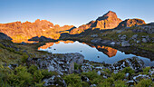 Sunrise over the foremost Lofoten island Moskenesøy with the illuminated peaks of Hermannsdalstinden (1029 m, right) and Ertenhelltinden (940 m, left) and their reflection in a small mountain lake, Lofoten, Norway, Scandinavia