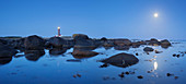 Gentle coast of the North Sea with the lighthouse Lista Lighthouse between boulders in blue twilight with moon, Farsund, Vest-Agder, Norway, Scandinavia