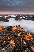 View from top of Skårasalen above the clouds to the surrounding peaks of the Sunnmøre Alps in the last evening sun, Alesund, More og Romsdal Fylke, Norway, Scandinavia