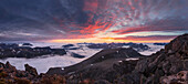 Wide view from top of Skårasalen (1542m) with an impressive sunset over the clouds and the mountains of the Sunnmøre Alps with rocks in foreground, Møre og Romsdal, Norway, Scandinavia