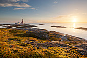 Romantic sunset above the lighthouse Tranøy Fyr on the coast of the Vest Fjord with cruise ship and the Lofoten wall in the background, Tranøya, Hamarøy, Nordland, Norway, Scandinavia