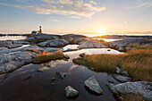Romantic sunset above the lighthouse Tranøy Fyr on the coast of the Vest Fjord with small lakes in the foreground, Tranøya, Hamarøy, Nordland, Norway, Scandinavia