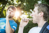 Young men brushing their teeth in the morning, Freilassing, Bavaria, Germany