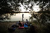 Three young men camping at a lake, Freilassing, Bavaria, Germany