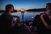 Three young men sitting at a lake at night, Freilassing, Bavaria, Germany