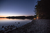 Three young men sitting at a lake and looking at the stars, Freilassing, Bavaria, Germany
