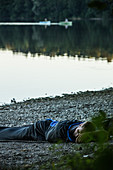 Young man camping at a lake only with a sleeping bag, Freilassing, Bavaria, Germany