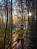 Young man running on a trail through a forest, Jogging, Allgaeu, Bavaria, Germany