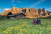 Passo Gardena, Dolomites South Tyrol, Italy. Children admire the alpenglow on the mountains of Sella