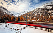 Bernina Express making its journey through the Swiss Alps, Engadine, Switzerland