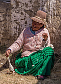 Ayamara woman in the typical costume working with a spindle. Aymaras are the native population of the Titicaca Lake area, in Bolivia, South America.