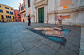Artwork of a madonnaro in front of the church of Santa Fosca in Venice with two men looking it.