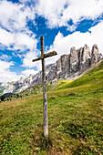 Ein großes Holzkreuz an einem Wanderweg vor der Bergkulisse am Sellajoch, Canazei, Dolomiten, Südtirol, Alto Adige , Italien