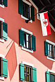 The Tyrol state flag at a town house with window shutters in the Old Town, Kitzbühel, Tyrol, Austria