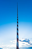 Ein typischer rot weiß geringelter Fahnenmast vor blauem Himmel und einer Bergkulisse, Radein, Südtirol, Alto Adige, Italien