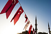 The minarets of the Blue Mosque, Sultan-Ahmed-Moschee, in the morning light between the national flags which hang over the Hippodrom, Istanbul, Turkey