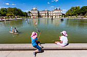 Girls play with sailing ships at the pond of the palace Palais du Luxembourg, Jardin du Luxembourg, 6.Arrondissement, Quartier Latin, Paris, France