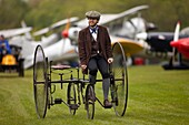 a man wearing Edwardian costume pushes a vintage museum piece Quadracycle, part of the Shuttleworth Collection, at an air display at Old Warden airfield,Bedfordshire,Britain.
