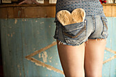 Rear view of a teenager girl with a heart in the shorts pocket.