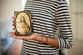 Closeup of young woman with striped shirt showing on their hands a picture of Jesus, Sacred Heart of Jesus