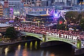 Australia, Victoria, VIC, Melbourne, White Nights Festival, buildings lit with projected laser designs, Federation Square and Princess Bridge, elevated view.