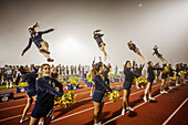 'Cheerleaders entertain the spectators at a high school night football game in San Juan Capistrano, CA, hold initials of the school name. Note ''flyers'' on shoulders of other cheerleaders.'