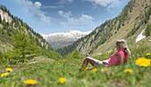 Woman in an alpine meadow, Canton of Graubünden, Switzerland
