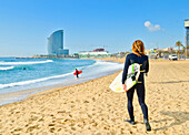 Surfers on Barceloneta beach. In the background W Barcelona hotel aka Vela Hotel designed by Ricard Bofill architect. Barcelona, Catalonia, Spain.