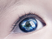Closeup of a child´s blue eye with the Earth globe, world map reflecting in it.