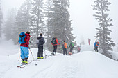 Group of touring skiers in alpine terrain in low light conditions, whiteout and fog - Germany Oberallgäu Oberstdorf