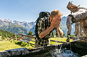 Hiker refreshing his face with cold water at a source