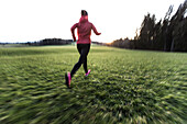 Young woman running over a field, Allgaeu, Bavaria, Germany