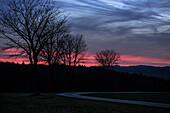 Abgeschiedene Straße zwischen Feldern und Wäldern beim Abendrot, Allgäu, Bayern, Deutschland