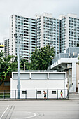 man and woman are running in park in front of residential towers, Kowloon, Hongkong, China, Asia
