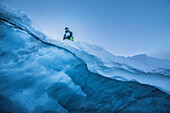 Young male snowboarder holding a big photo flash on a glacier, Pitztal, Tyrol, Austria