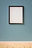 Black picture frame on a blue wall.