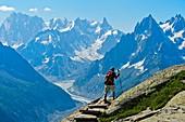 Hiker in the Aiguilles Rouges National Nature Reserve, view at the peaks Grandes Jorasses und Dent du Géant, Chamonix, Haute-Savoie department, France.