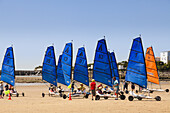 Group of children learning sand yachting on a beach.